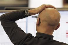 Un trader davanti allo schermo all'IG Index di Londra, lo scorso 9 dicembre. REUTERS/Finbarr O'Reilly
