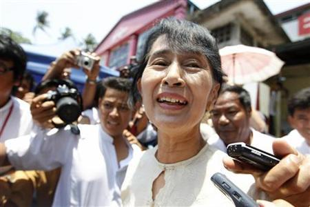 Myanmar's pro-democracy leader Aung San Suu Kyi talks to reporters after a party meeting in front of the National League for Democracy (NLD) party's head office in Yangon April 20, 2012. REUTERS/Soe Zeya Tun