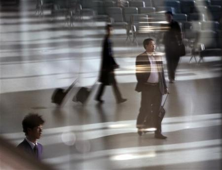Passengers reflect on a glass wall as they walk inside terminal 2 of Shanghai Hongqiao International airport on its first day of operation, March 16, 2010. REUTERS/Nir Elias