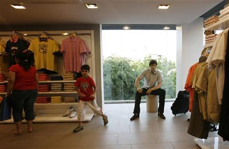 A mannequin is on display beside a window as people shop in a clothes shop in New Delhi June 17, 2007. REUTERS/Desmond Boylan/Files