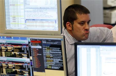 A trader gestures in front of his screens during a bond auction on a trading floor in Madrid, April 19, 2012. Spain entered its second recession since 2009 in the first quarter after more than four years of contraction or minimal growth in the aftermath of a collapse in its property market. REUTERS/Andrea Comas