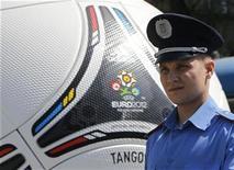 Ucrania describió el lunes las amenazas de varios países europeos de boicotear la Eurocopa de fútbol que albergará en junio como un retorno de las tácticas de la Guerra Fría, después de que varios dirigentes cancelaran sus visitas por el trato a una destacada política de la oposición. En la imagen, un policia junto a un modelo gigante del balón oficial de la Eurocopa el 28 de abril de 2012 en Dnipropetrovsk. REUTERS/Gleb Garanich