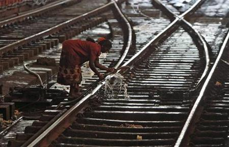 A worker uses a hose to clean between tracks at a railway station in Chennai March 14, 2012. REUTERS/Babu/Files