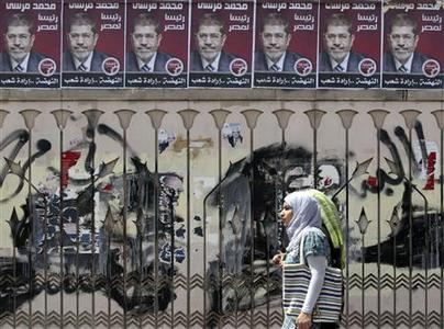 Women walk under campaign election posters for Mohamed Mursi, the head of the Muslim Brotherhood's political party, and the Brotherhood's new presidential candidate in Cairo April 29, 2012. REUTERS/Amr Abdallah Dalsh