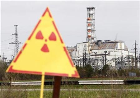 A hazard sign indicating radiation is seen in front of a containment shelter for the damaged fourth reactor at the Chernobyl nuclear power plant April 24, 2012. REUTERS/Gleb Garanich