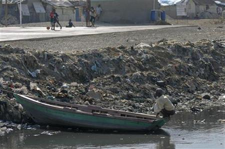 A man uses a canal as a toilet as he squats on a boat in the slum area of Cite de Dieu, just outside Port-au-Prince March 13, 2012. REUTERS/Swoan Parker/Files