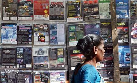 A woman walks past pirated DVDs and software on sale at a street side hawker shop in Mumbai November 12, 2009. REUTERS/Arko Datta/Files