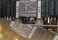 Tras confirmar el Instituto Nacional de Estadística que España entró en su segunda recesión en tres años, la bolsa española retomó el lunes la senda descendente tras el espejismo del viernes en una jornada en la que se dejó casi un dos por ciento de su valor. En la imagen de archivo, un operador de bolsa habla por su teléfono móvil delante del panel de cotizaciones de la Bolsa de Madrid, el 10 de abril de 2012. REUTERS/Andrea Comas