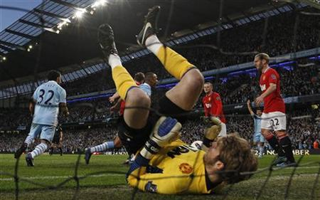 Manchester United goalkeeper David de Gea lies on the ground after being beaten by Manchester City's Vincent Kompany (3rd L, partially obscured) during their English Premier League soccer match at the Etihad stadium in Manchester, northern England April 30, 2012. REUTERS/Darren Staples