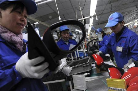 An employee is reflected on a rear view mirror at an assembly line of car components in Jiaxing, Zhejiang province February 2, 2012. REUTERS/Stringer