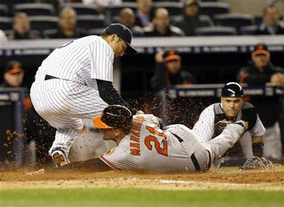Baltimore Orioles Nick Markakis (C) is tagged out by New York Yankees starting pitcher Hiroki Kuroda (L) after a wild pitch by Kuroda during the seventh inning of their MLB American League baseball game at Yankee Stadium in New York, April 30, 2012. New York Yankees catcher Russell Martin looks on after throwing the ball to Yankees Kuroda. REUTERS/Adam Hunger