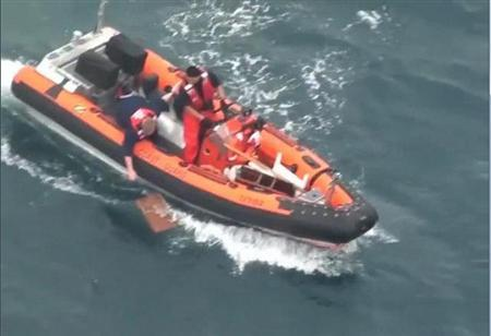 A member of the U.S. Coast Guard reaches for a piece of flotsam during their search for the lone missing crew member of the yacht Aegean off the California coast in this April 29, 2012 frame grab from video. The Aegean went missing April 28, 2012 during the Newport to Ensenada Yacht Race off the coast of California. REUTERS/U.S. Coast Guard/Handout