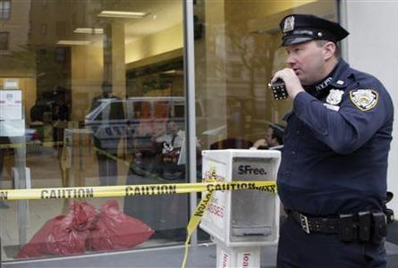 A New York City police officer talks on the radio, outside a window where bags containing clothes are seen at a Wells Fargo bank branch that received suspicious envelopes containing white powder, in New York City April 30, 2012. The company closed three branches in the city that received the packages on Monday. REUTERS/Lee Celano