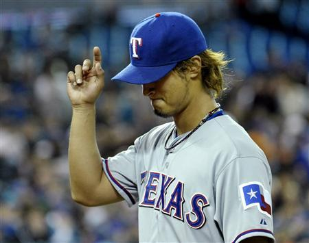 Texas Rangers pitcher Yu Darvish gestures to fans during the second inning of their MLB American League baseball game against the Toronto Blue Jays in Toronto April 30, 2012. REUTERS/Mike Cassese