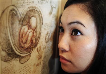 Employee Hanae Tsuji poses with artist Leonardo da Vinci's drawing ''studies of the foetus in the womb c.1510-13'' at the Queen's Gallery at Buckingham Palace in London April 30, 2012. REUTERS/Luke MacGregor