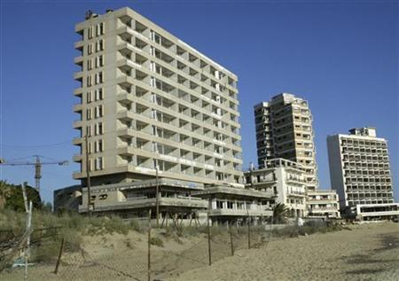A view of the abandoned Greek Cypriot neighbourhood of Varosha in this May 2, 2003 file photo. Derelict apartment blocks and crumbling hotels riddled with bullet holes sit on empty beaches behind barbed-wire fencing after Varosha's 15,000 residents fled in 1974, when a Turkish invasion sparked by a Greek-inspired coup split Cyprus. However, if peace talks between estranged Greek and Turkish Cypriots succeed, Varosha could be one of the first Greek Cypriot areas to be revived, one of scores of abandoned areas creating a buffer separating the island's Turkish and Greek populations for three decades. REUTERS/Andreas Manolis/Files