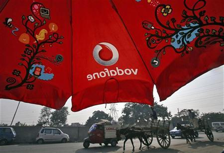Men ride their horse carts past an umbrella with a Vodafone logo on a road in Jammu November 21, 2011. REUTERS/Mukesh Gupta/Files