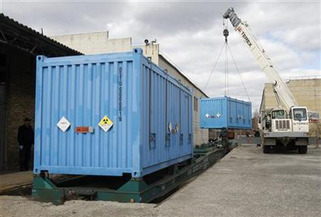 Workers place a container with spent highly-enriched uranium on a train at a railway station near Kiev March 24, 2012. Picture taken March 24, 2012. REUTERS/Gleb Garanich/Files