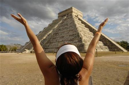 A woman raises her arms to receive energy from the sun at the Mayan pyramid El Castillo (The Castle), in Chichen Itza, in the southern state of Yucatan, Mexico March 21, 2009. REUTERS/Argely Salazar