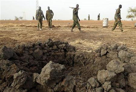 South Sudan's army, or the SPLA, soldiers walk past a fox hole on the frontline in Panakuach, Unity state, April 24, 2012. REUTERS/Goran Tomasevic