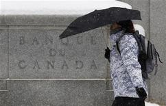 A pedestrian holding an umbrella walks past the Bank of Canada building during a snow fall in Ottawa January 17, 2012. REUTERS/Chris Wattie