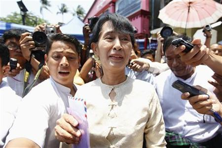 Myanmar's pro-democracy leader Aung San Suu Kyi (C) talks to reporters after a party meeting in front of the National League for Democracy (NLD) party's head office in Yangon April 20, 2012. REUTERS/Soe Zeya Tun