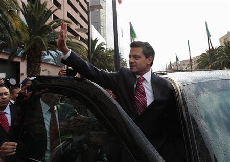 Enrique Pena Nieto (C), presidential candidate of the opposition Institutional Revolutionary Party (PRI), waves to supporters after attending a private meeting with Spanish's Prime Minister Mariano Rajoy at a hotel in Mexico City April 18, 2012. REUTERS/Henry Romero