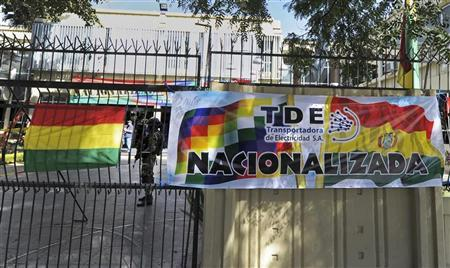 A banner that reads ''TDE Nationalized,'' hangs in front of Bolivian soldiers surrounding the headquarters of the electric company Transportadora de Electricidad (TDE), belonging to Spain's Electrica Espanola, after President Evo Morales announced its nationalization in Cochabamba, May 1, 2012. REUTERS/Danilo Balderrama