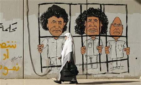 A woman walks past graffiti on a wall of former Libyan leader Muammar Gaddafi (C), his son Saif al-Islam Gaddafi (R) and former head of the Libyan Intelligence Service Abdullah Al-Senussi in Tripoli November 20, 2011. REUTERS/Mohammed Salem