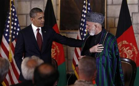 U.S. President Barack Obama puts his arm on Afghan President Hamid Karzai after they signed the Strategic Partnership Agreement at the Presidential Palace in Kabul, May 2, 2012. REUTERS/Kevin Lamarque