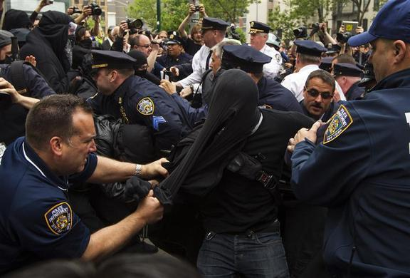 New York Police Department officers struggle to tear the mask off of an Occupy Wall Street activist as he is detained during a march through the streets of Manhattan, May 1, 2012.  REUTERS-Lucas Jackson