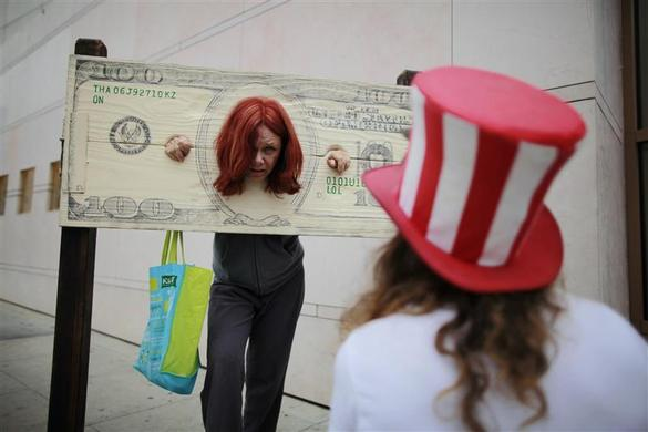 Victoria Becker is shown in a pillory shaped like a $100 bill during May Day demonstrations in Beverly Hills, May 1, 2012.REUTERS-Lucy Nicholson