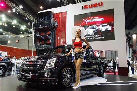 A model poses next to Isuzu vehicles during the 31st Bangkok International Motor Show in Bangkok March 26, 2010. REUTERS/Chaiwat Subprasom