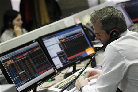 Traders talk on the phone during a Spanish Treasury bills auction at a private bank in Madrid, April 17, 2012. REUTERS/Andrea Comas