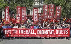 "Workers and union members hold banners and flags of the General Workers Union (UGT) and Comisiones Obreras (CCOO) during a Labour Day march in central Valencia May 1, 2012. The banner reads, ""Work, dignity, rights, they want to end all of it."" REUTERS/Heino Kalis"