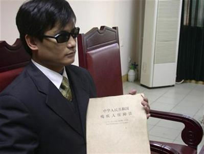 Blind legal activist Chen Guangcheng holds a document that reads: ''Law of the People's Republic of China on the Protection of Disabled Persons'', in this undated handout. U.S. Secretary of State Hillary Clinton arrived in China on May 2, 2012, for top-level talks that risk being upstaged by the fate of Chen, a blind dissident whose supporters say is under U.S. protection in Beijing after escaping house arrest. REUTERS/www.ChinaAid.or/Handout