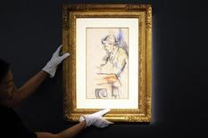 """Сотрудница Christie's держит картину Поля Сезанна """"Игрок в карты"""" во время пресс-показа в Нью-Йорке 26 апреля 2012 года. Весенние продажи аукционного дома Christie's успешно стартовали во вторник: с молотка ушли работы Поля Сезанна и Анри Матисса за $19 миллионов каждая. REUTERS/Keith Bedford"""