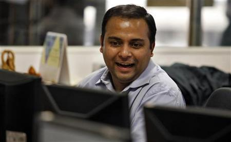 A broker smiles as he trades on his computer terminal at a stock brokerage firm in Mumbai December 31, 2009. REUTERS/Punit Paranjpe/Files