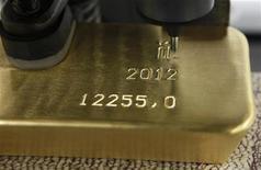 Автомат наносит гравировку на золотой слиток на заводе Красцветмет в Красноярске 12 апреля 2012 года. Цены на золото снижаются из-за ослабления евро к доллару после публикации слабых производственных показателей еврозоны и сильной статистики США. REUTERS/Ilya Naymushin