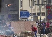 Протестующие кидают бутылки с зажигательной смесью во время столкновений сторонников и противников исламистов в Каире 2 мая 2012 года. Одиннадцать человек погибли и более 160 были ранены около министерства обороны Египта в среду, после того как вооруженные люди напали на протестующих, требовавших прекратить правление военных. REUTERS /Asmaa Waguih