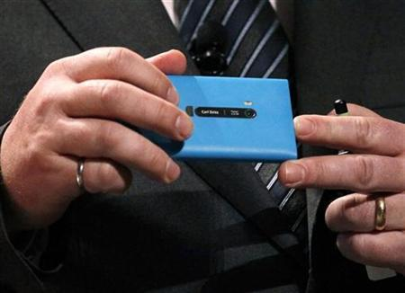Nokia CEO Stephen Elop shows the Carl Zeiss lens on the back of the Nokia Lumia 900 smartphone at a Nokia press event at the Consumer Electronics Show opening in Las Vegas January 9, 2012. REUTERS/Rick Wilking