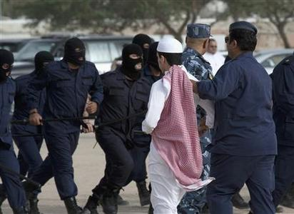 A Kuwait Special Forces officer removes a stateless protester after a rally in Kuwait's Tiama district May 1, 2012. Kuwaiti riot police used batons and armored trucks to disperse a group of about 200 stateless protesters, known in Arabic as ''bidoon'' and numbering up to 180,000 people, on Tuesday, the latest rally by descendants of mainly desert nomads seeking improved rights in the oil-exporting Gulf state. REUTERS/Hani Abdullah