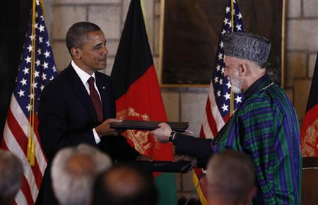U.S. President Barack Obama (L) and Afghan President Hamid Karzai exchange documents after signing the Strategic Partnership Agreement at the Presidential Palace in Kabul, May 2, 2012. REUTERS/Kevin Lamarque