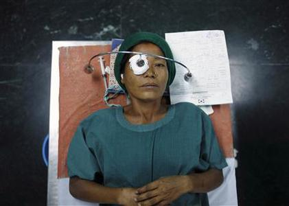A patient with cataract lies on a hospital bed upon receiving anesthesia during a cataract surgery at the Tilganga Eye Center in Kathmandu April 25, 2012. About 150,000 of Nepal's 26.6 million people are estimated to be blind in both eyes, most of them with cataracts. Picture taken April 25, 2012. REUTERS/Navesh Chitrakar
