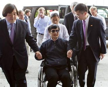 A handout photo from US Embassy Beijing Press office shows blind activist Chen Guangcheng (2nd L) sitting in a wheelchair as he is accompanied by U.S. Ambassador to China Gary Locke (2nd R) at a hospital in Beijing, May 2, 2012. REUTERS/US Embassy Beijing Press Office/Handout