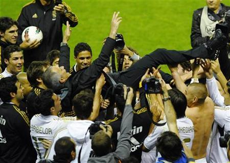 Real Madrid's coach Jose Mourinho is thrown in the air by his players after their win over Athletic Bilbao to win the Spanish first division league title at San Mames stadium in Bilbao May 2, 2012. REUTERS/Vincent West
