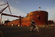 An employee rides a bicycle past a nearly completed ship at China State Shipbuilding Corporation (CSSC) Longxue shipbuilding, in the southern Chinese city of Guangzhou November 13, 2011. REUTERS/Tyrone Siu