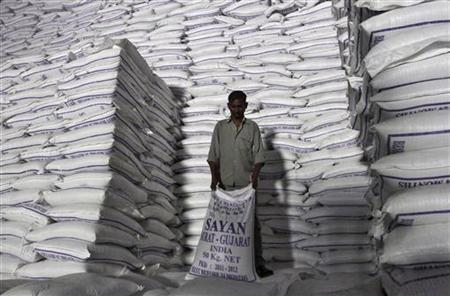 A worker shifts a sack of sugar at a godown inside a sugar factory at Sanyan village in Gujarat April 23, 2012. REUTERS/Amit Dave