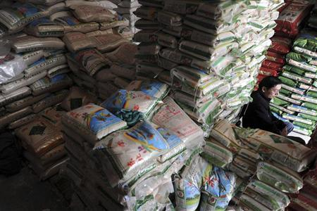 A vendor sits among stacks of rice as he waits for customers at a food wholesale market in Hefei, Anhui province April 6, 2012. REUTERS/Stringer