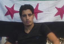 "Abdelbasset Saroot, former Syria international goalkeeper, is seen in front of opposition flag in this undated photograph received on May 2, 2012. Syrian opposition has said on Wednesday that Abdelbassed was wounded by pro government sniper in Al Khalidieh in Homs on Wednesday but is in good health. 20-year-old Saroot said on Tuesday his country's athletes do not want to compete in this year's London Olympics because ""they don't want to play for a flag that they have no pride or faith in"" in an interview with ITV News. REUTERS/Handout"